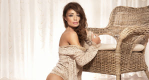 Sensual brunette beauty sitting in bright room, looking at camer. Photo of sexy, sensual, beautiful brunette woman wearing lace clothes, sitting on the floor Stock Photos