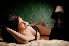 Sensual brunette in bed on green vintage background Stock Photo