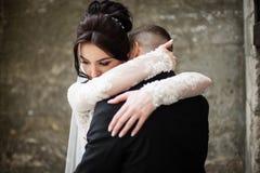 Sensual brunette bride hugging groom in black suit closeup, wall Stock Photos