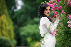 Sensual brunette bride posing and smelling pink roses in park Royalty Free Stock Photos