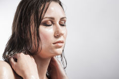 Sensual Brunette with Closed Eyes Showing Wet and Shining Skin and Wet Hair. Creative Makeup Stock Photography