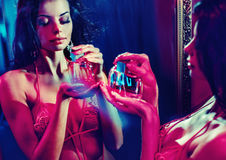 Sensual brunette lady holding a bottle of perfume Stock Photo