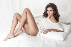 Sensual brunette lady posing in bed Stock Images