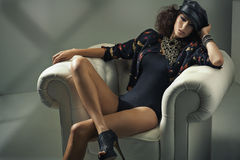 Sensual brunette lady sitting in the soft armchair royalty free stock image