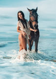 Sensual brunette lady walking with the majestic horse stock photo