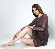 Sensual brunette posing in brown lace gown Stock Image