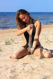 Sensual brunette pouring sand on beach Stock Photography
