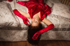 Sensual brunette in a red dress lying on the bed Royalty Free Stock Photos