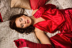 Sensual brunette in a red dress lying on the bed Stock Image