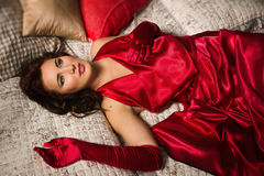 Sensual brunette in a red dress lying on the bed Stock Photo