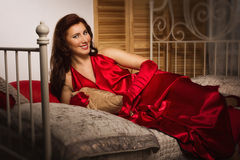 Sensual brunette in a red dress sitting on the bed Stock Photo
