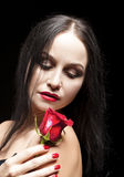 Sensual Brunette with Red Flower Against Black Background Stock Photography
