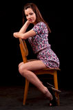 Sensual brunette sitting and posing on a chair against a black b Royalty Free Stock Images