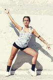 Sensual brunette tanned girl wall behind. Arms and legs spread Royalty Free Stock Images