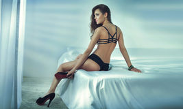 Sensual brunette woman in bed. Stock Photos