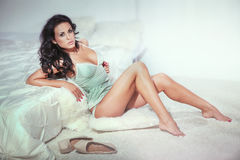 Sensual brunette woman in bedroom Stock Images