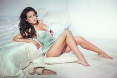 Sensual brunette woman in bedroom Stock Images