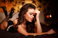 Sensual brunette woman laying on bed Stock Photography
