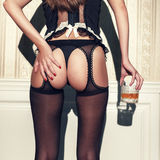 Sensual brunette woman in lingerie holding glass of whiskey Royalty Free Stock Image