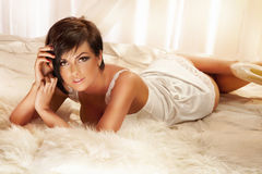 Sensual brunette woman lying and posing Royalty Free Stock Photos