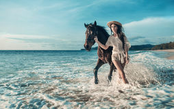 Sensual brunette woman walking with a majestic horse stock image