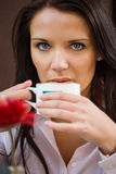 Sensual businesswoman with coffee, isolated on brown background. Stock Photos