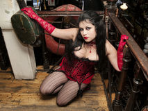 Sensual cabaret woman with railing. Cabaret woman portraited in a bar in red corset Royalty Free Stock Images