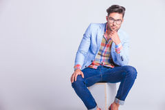 Sensual casual man wearing glasses and jeans seated Royalty Free Stock Photo