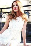 Sensual Caucasian young woman model with evening makeup in white summer dress posing on the street background. Glamor beauty portrait of beautiful sensual royalty free stock image
