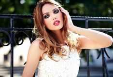 Sensual Caucasian young woman model with evening makeup in white summer dress posing on the street background. Glamor beauty portrait of beautiful sensual royalty free stock photo