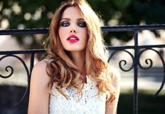 Sensual Caucasian young woman model with evening makeup in white summer dress posing on the street background. Glamor beauty portrait of beautiful sensual stock image