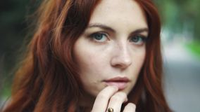 Sensual closeup portrait of beautiful red-haired girl outdoors. 20s. Closeup portrait of a beautiful red-haired girl. hair fluttering in the wind. girl with stock footage