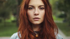 Sensual closeup portrait of beautiful red-haired girl in a summer Park. 20s. Closeup portrait of a beautiful red-haired girl. hair fluttering in the wind. girl stock video footage