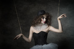 Sensual clown puppet female. Uncombed sensual woman with gothic puppet costume, uncombed hair and clown make-up. She wearing vintage tutu and bowler Royalty Free Stock Images