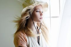 Sensual Country Woman in Hat. Portrait. Cowgirl in Hat near the window. Beautiful Young Blonde Stock Images