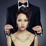 Sensual couple. Elegant men on a beautiful women wears a necklace Stock Images