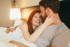Sensual couple in bed being romantic. Sensual couple in bed cuddling royalty free stock photo