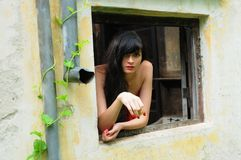 Beautiful young brunette woman in the window. Sensual and cute gypsy brunette woman in the window Stock Photography