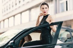 Sensual dangerous woman standing with a feline look in the door. Of a car wearing a stylish black romper, elegant bun and red lips with a blurred building in stock images
