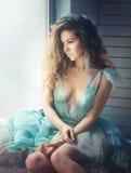 Sensual dreaming woman portrait sitting on a big window Royalty Free Stock Photo