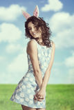 Sensual easter girl. Smiling brunette female in easter shoot posing with curly hair-style pink bunny ears and spring dress Royalty Free Stock Images