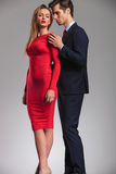 Sensual elegant couple standing embraced. Men behind women in red dress holding her close Royalty Free Stock Photos