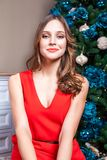Sensual woman in a beautiful red dress and makeup looking at camera with passion. Stock Images
