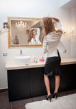 Sensual elegant woman in office outfit looking into a large mirror. Beautiful and sexy blonde young woman wearing an white jacket Stock Image