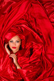 Sensual face  in red satin fabric. Sexy sensual face with aggressive make-up in red satin fabric Royalty Free Stock Image