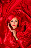 Sensual face  in red satin fabric. Sexy sensual face with aggressive make-up in red satin fabric Stock Images