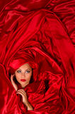 Sensual face  in red satin fabric Royalty Free Stock Photography