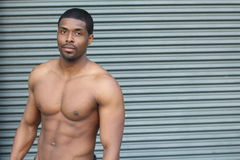 Sensual fashion portrait of a fit nude African male model posing against modern gray background with copy space Stock Image