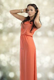 Sensual fashion woman. Cute female with elegant style and long brown hair, wearing orange dress and bracelets, sensual pose Stock Photo