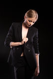 Sensual fashionable woman in suit on black background. In studio photo. Glamour and elegance Stock Photo